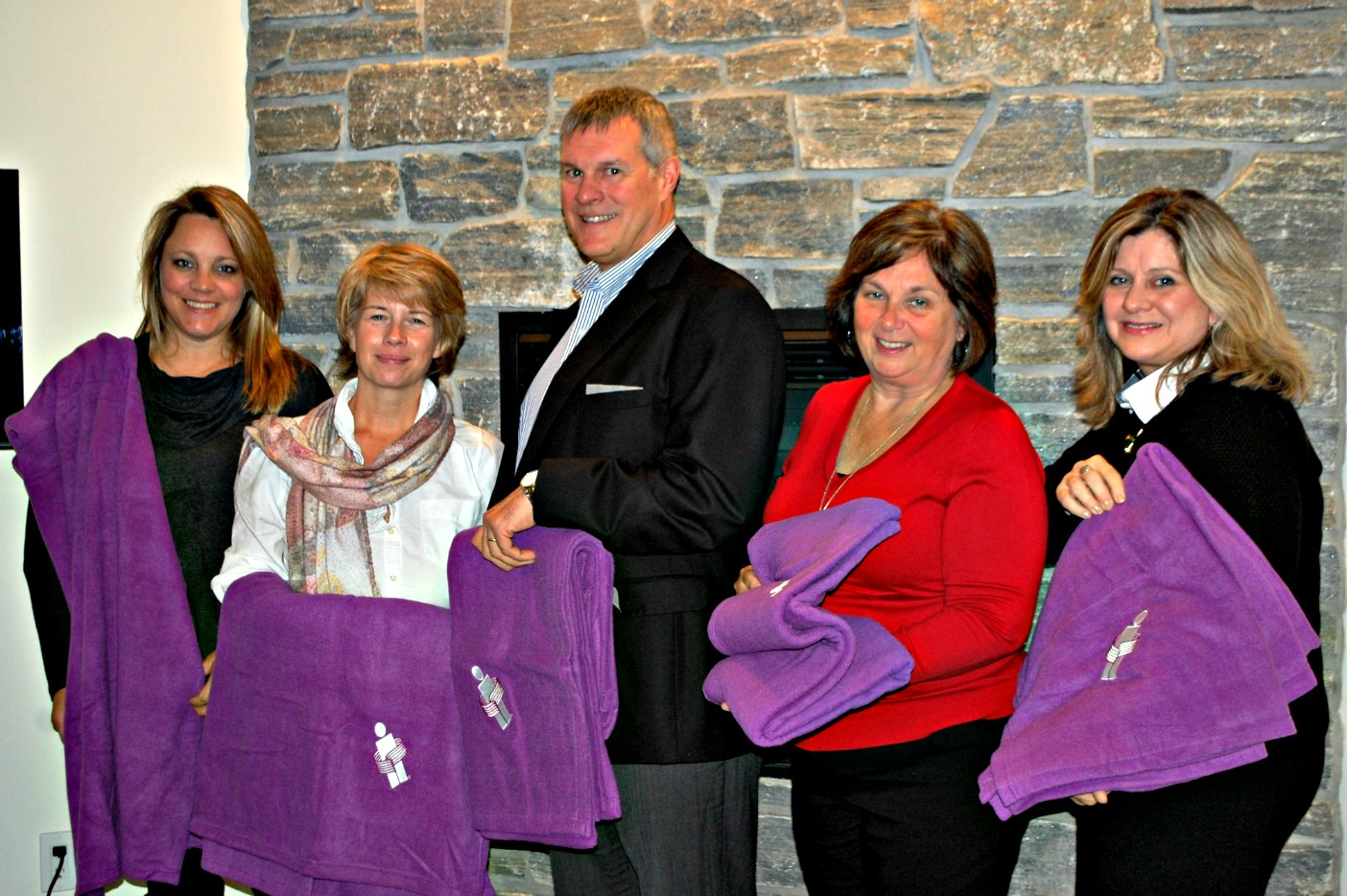 Andrea Hadlington (left), Deane Belfry (centre) and Karen Armstrong (right) present blankets to Melissa Polischuk and Bev Lashbrook from Hospice Huntsville