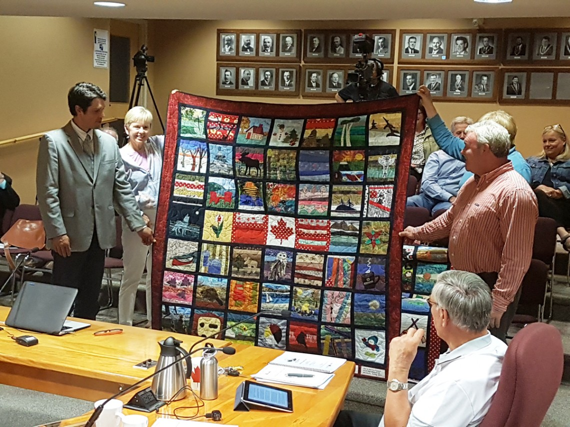 Mary Spring (back left) and Terri Howell (back right) present their labour of love, received on behalf of the Town by councillors Jonathan Wiebe (front left) and Jason FitzGerald (front right).