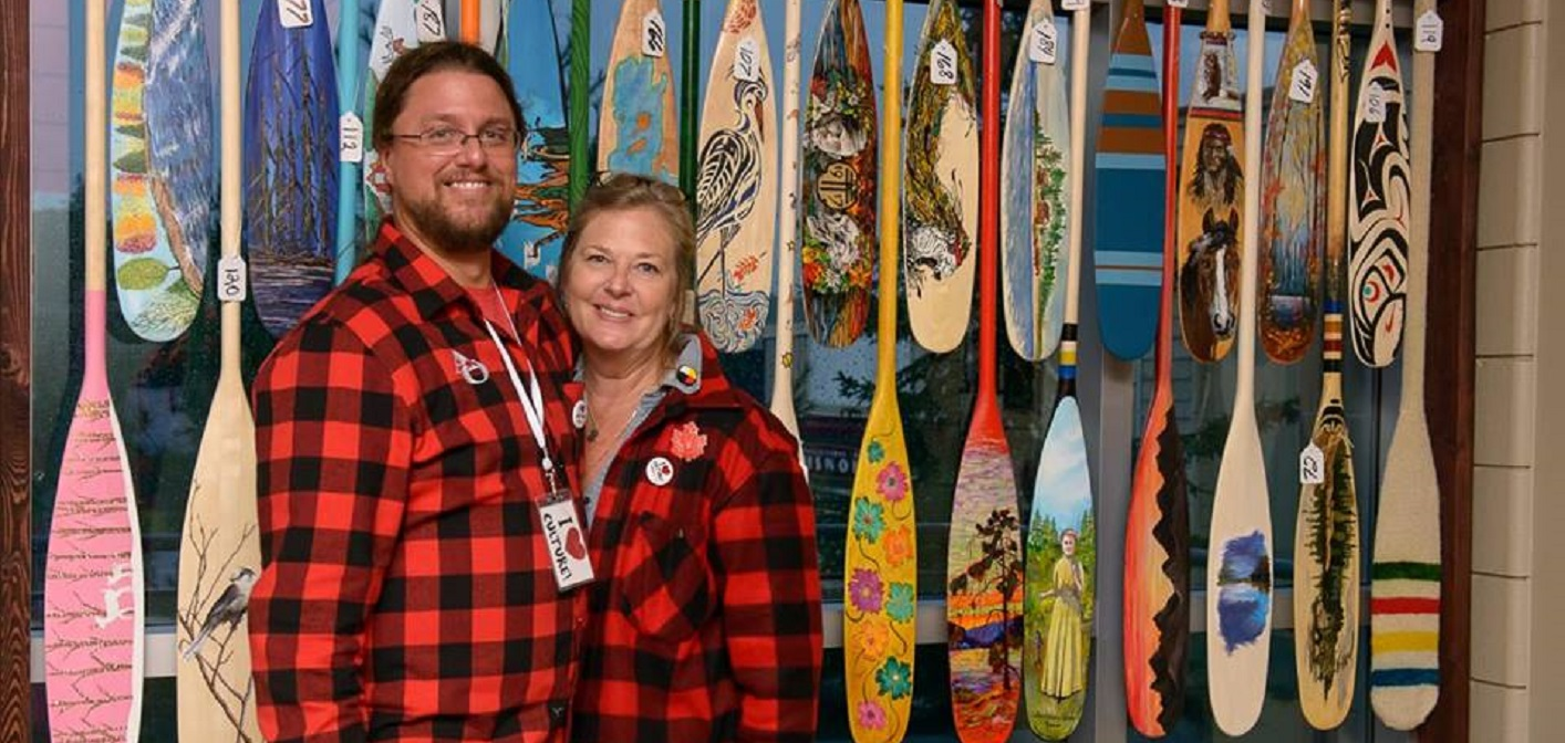 Randy Mitson, Algonquin Outfitters' Marketing Director, and Teri Souter, the Town's Manager of Arts, Culture and Heritage at the paddle art auction