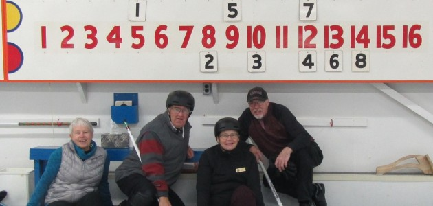 (From left) Barb Burton, Ted Bionda, Susan Bionda and John McDonald in front of the scoreboard showing their eight-rock end (Photo courtesy of Huntsville Curling Club)