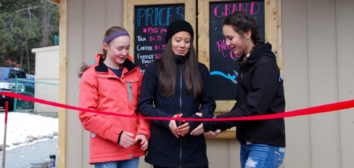 Ava Bijl (middle), the Classroom Economy president, is joined by Grace Gaughan, the VP of Special Operations, and Sage Nakamoto, the past president, to cut the ribbon on the new building for the café.