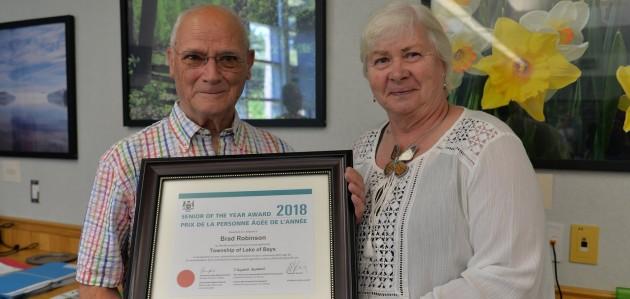 Brad Robinson (left) receives the Lake of Bays 2018 Senior of the Year award from Deputy Mayor Nancy Tapley (supplied photo)