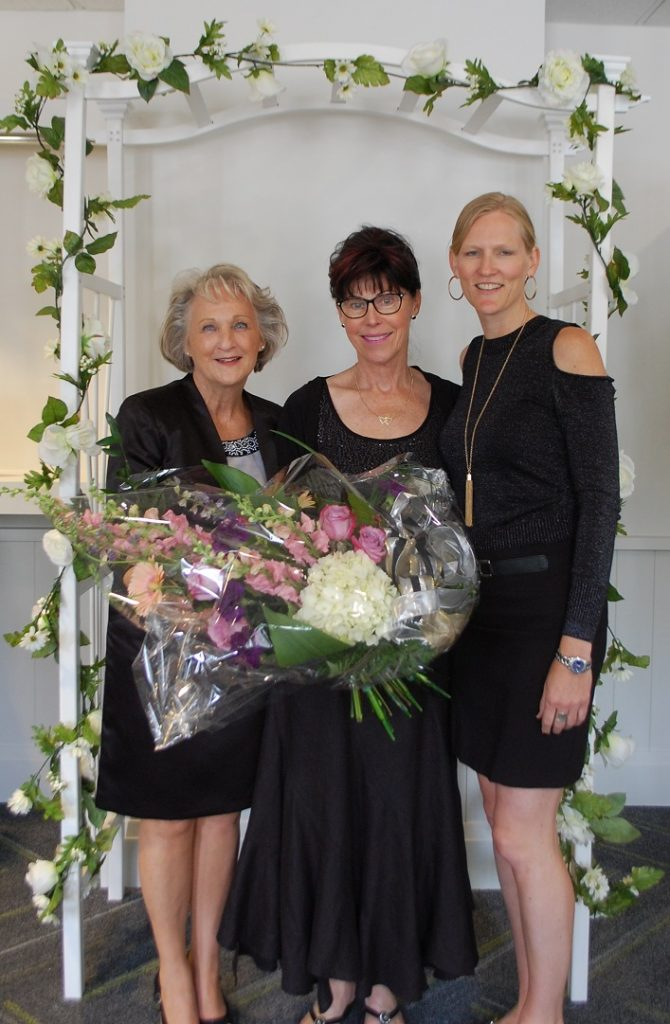 Donna Nairn (left) and Sarah Caswell (right) presented a bouquet to Karen Waters in recognition of 20 years of employment with the organization