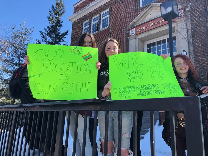 (From left) Charlotte MacDonald, Kailey Sobieraj, and Victoria Jones used signs to emphasize their opposition to education cuts