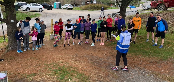 Participants in the first-ever parkrun in Huntsville listen to instructions before heading out on the trail