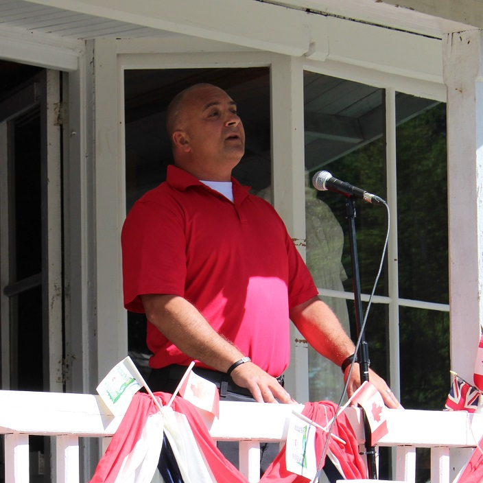 Huntsville Lake of Bays Fire Department Captain Paul Calleja leads the crowd in O Canada