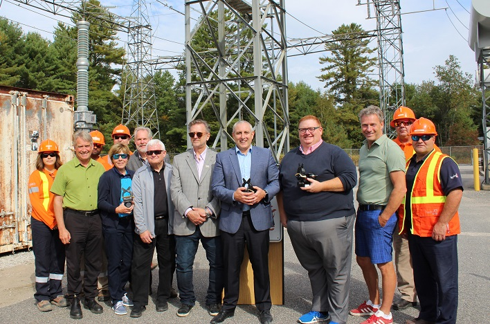 Hydro One chief corporate affairs and customer care officer Jason Fitzsimmons (front, third from right) with Hydro One workers (in orange), Parry Sound-Muskoka MPP Norm Miller (front left) and the mayors of Muskoka's six municipalities (front from second left) Karin Terziano (Huntsville), Peter Koetsier (Georgian Bay), Paul Kelly (Gravenhurst), Terry Glover (Lake of Bays), Graydon Smith (Bracebridge) and Phil Harding (Muskoka Lakes)