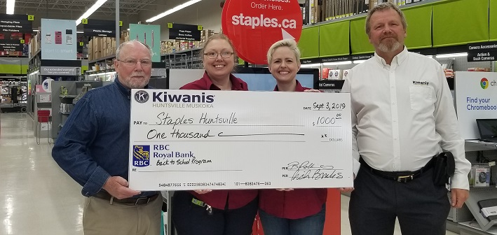 Rick Brooks (left) and Martin Mann (right) of the Kiwanis Club of Huntsville Muskoka present a cheque to Bet Jones and Karen Crowe of Staples (supplied)