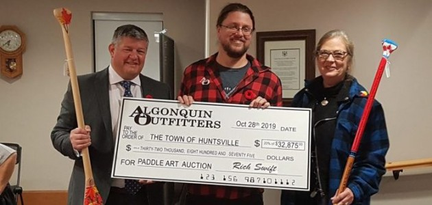 Huntsville Mayor Scott Aitchison, Algonquin Outfitters marketing director Randy Mitson, and Huntsville manager of arts, culture and heritage Teri Souter hold up two of the paddles entered in the auction and a cheque for the proceeds that will be shared by five arts organizations