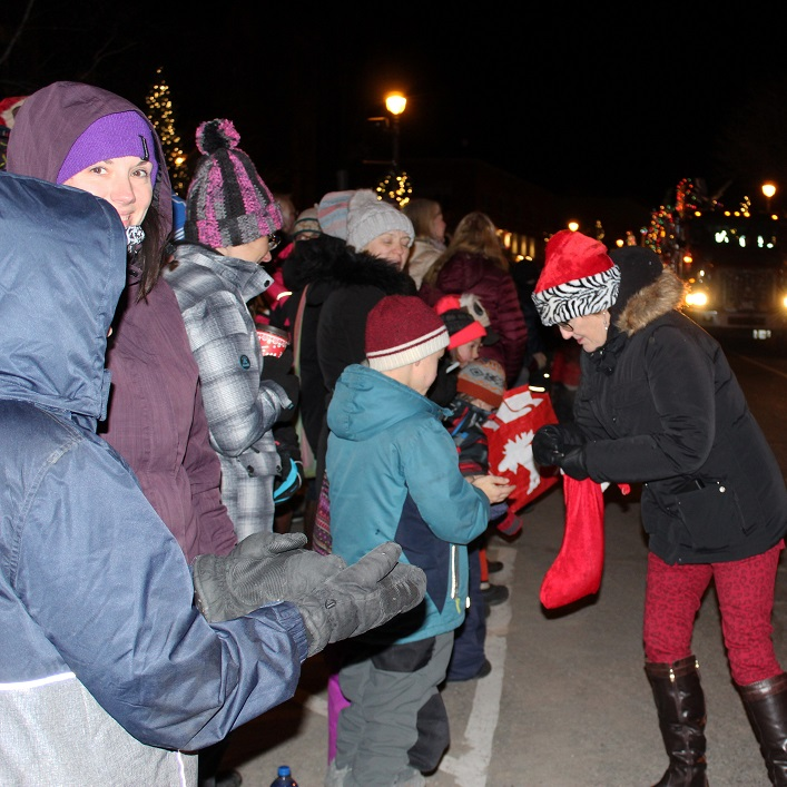 Kids along the parade route were ready for the candy bonanza. Here Councillor Nancy Alcock shares some sweet treats.