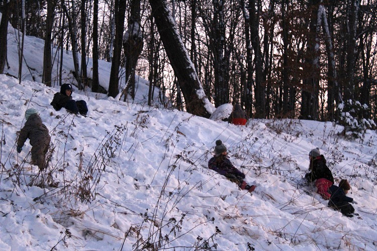 Kids took advantage of the snow-covered hill in the fading light for some impromptu sliding