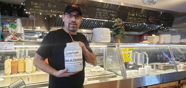 Shaun Israelstam holds the donation jar at Algonquin Café (Mandi Hargrave)