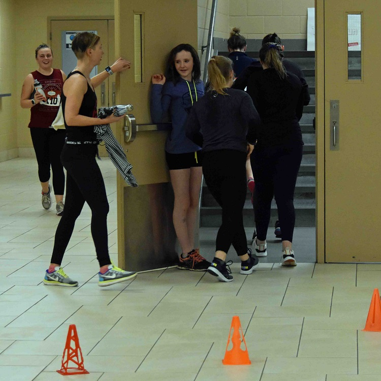 Volunteer Lauchlyn Trenholm, 11 (holding the door), directs participants to the track for the final leg of the indoor tri (Cheyenne Wood)