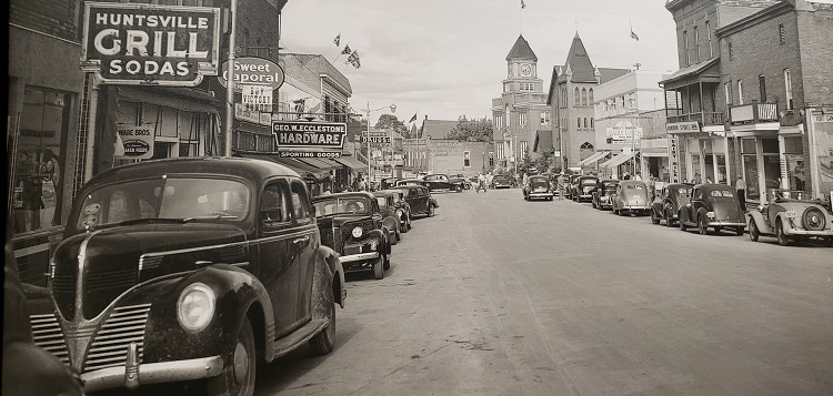 "Main Street, Huntsville, 1940s. Town Hall, with its easily recognizable clock tower, is a prominent part of downtown Huntsville.  ""Notice the Union Jack and the advertisement for Victory Bonds,"" writes Martha Briggs Watson. ""A little before my time of conscious memory, but pretty close!"" (courtesy of Martha Briggs Watson)"