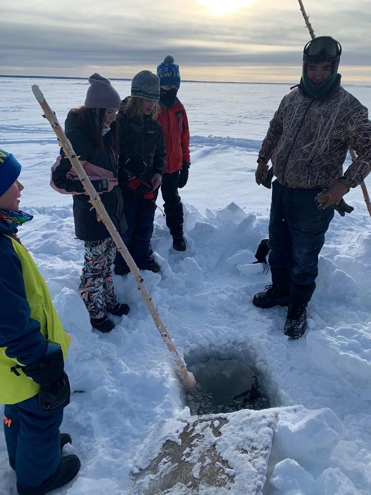 Grade 6 Tawingo students (Matthew Hochfellner, Emma Cole, Tobin Spiers, James Laughton) ice fishing with Elder Ernest near Horn River (supplied)