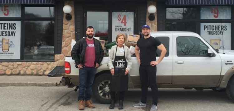 Lynne Doyle (centre), of The Table Soup Kitchen Foundation, picks up food donated by Chuck's Roadhouse (The Table Soup Kitchen Foundation / Facebook)