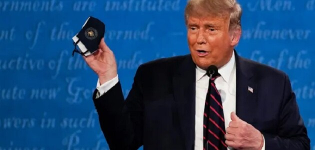 US President Donald Trump holds up a face mask at the first presidential debate (Julio Cortez / Associated Press)