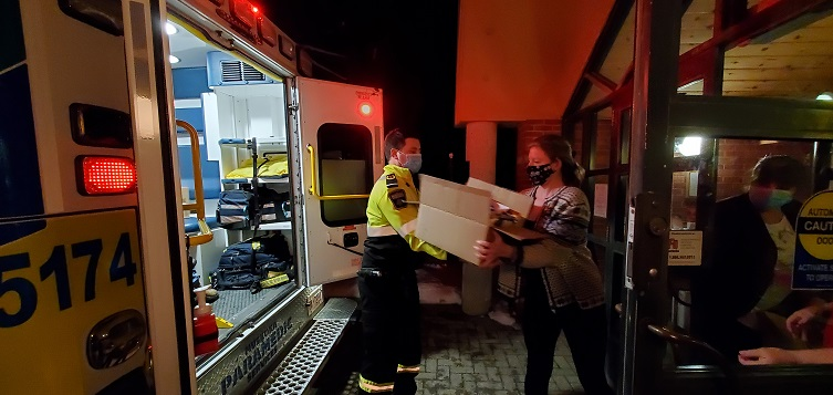A paramedic hands a box of donations to a volunteer at the Salvation Army for Project Porchlight 2020 (Dawn Huddlestone)