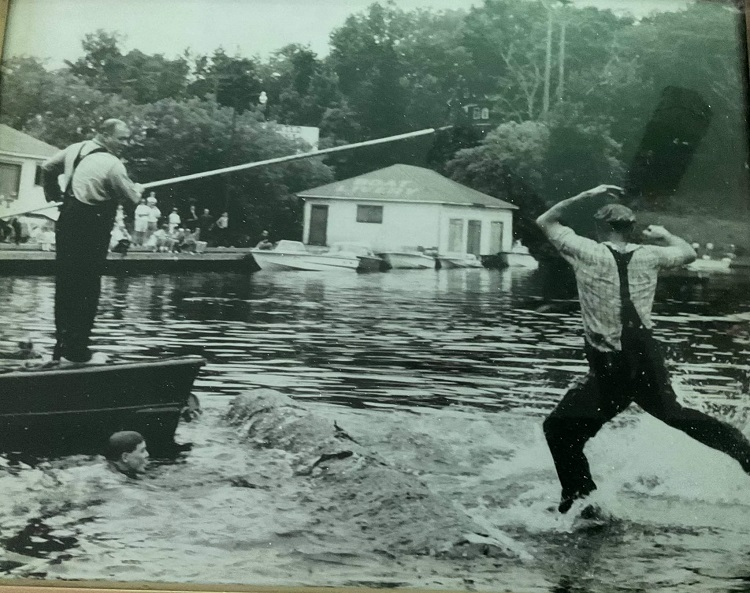 Percy Wagg (standing) watches an unknown man roll the log (courtesy of Jean Wagg)