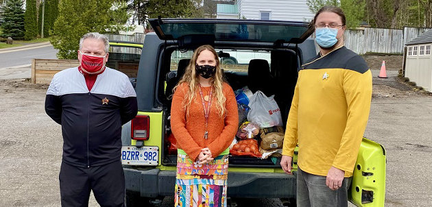 Rob Ehl (left) and Randy Mitson (right) deliver donated food to Heather Cassie at The Table (submitted photo)